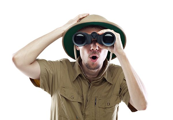 Young man wearing safari shirt and pith helmet looking through binoculars with a surprised expression isolated on white