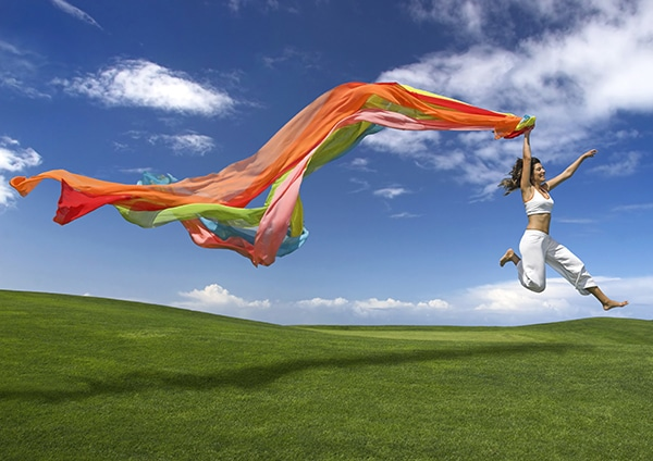 Woman with rainbow scarf jumping