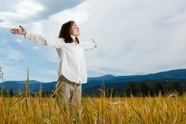 Woman holding arms up against blue sky